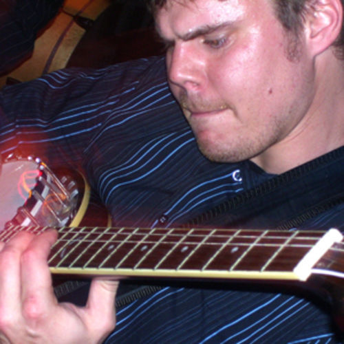 Matt Clark, hitting a high chord on a six-string banjo