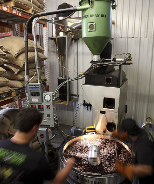 Workers roast premium coffee beans on a fluid head roaster at Katz Coffee.