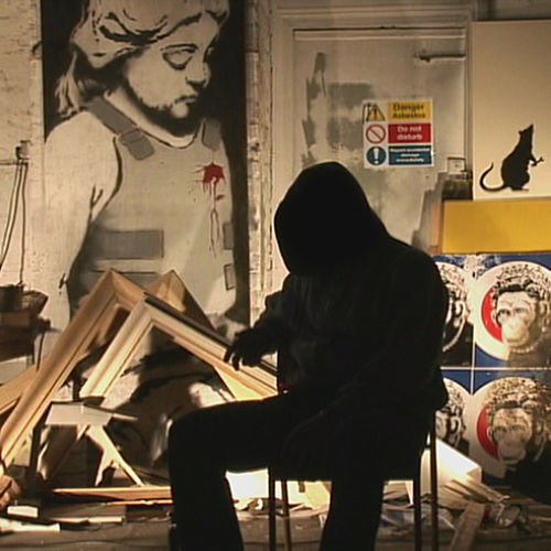 Banksy appears faceless under a dark hood.