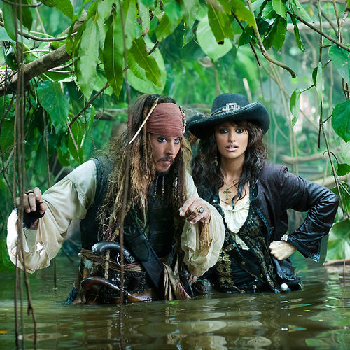 Johnny Depp and Penélope Cruz wade through a mess.