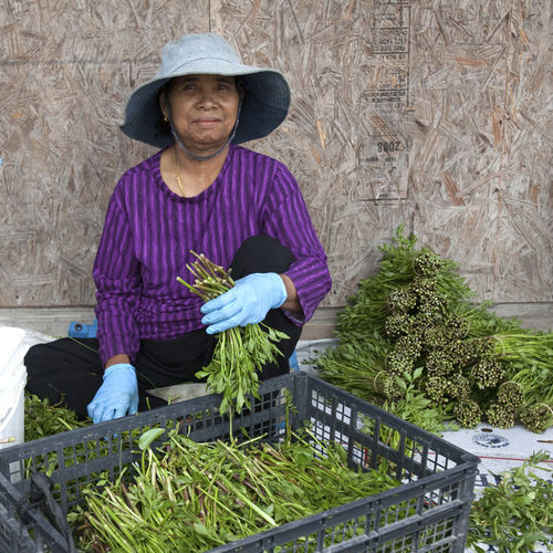 Lay Ut, 67, only recently came to the United States from Cambodia and spends every day hunched and bundling water spinach. She says her life in America is the same as it was in Cambodia.