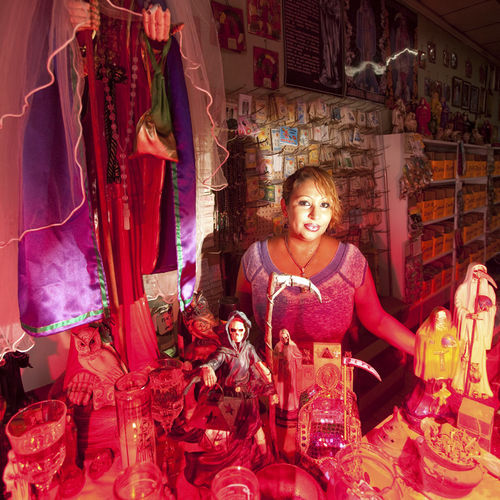 "Maria stands beside her public Santa Muerte altar inside her Sharpstown botánica. The Veracruz-born Santa Muerte priestess keeps another altar in her office and a truly awe-inspiring one in her back room. She won't allow that one to be photographed. ""It's my religion,"" she says. Click here to see a video interview with Maria."