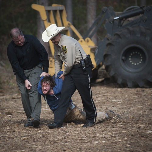 Members of the Cherokee County Sheriff's Department drag away a protester who chained himself to construction equipment.