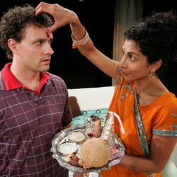 Zareen (Rahnuma Panthaky, right) demonstrates a Parsi wedding custom to her daughter's boyfriend David (Luke Eddy).
