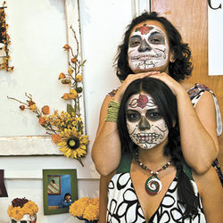 Eve Suarez (top) and Iris Contreras truly get into the spirit of the Day of the Dead. The pair took second place in the altar-creation category at MECA's weeklong celebration, honoring ancestors who have passed away. To view image larger, click here.