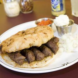 Difficult to pronounce -- and delicious: Cevapcici and lepinja with ajvar, kajmak and chopped onions.