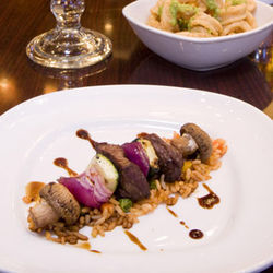 Appetizers like beef brochette and calamari are a hit at happy hour.
