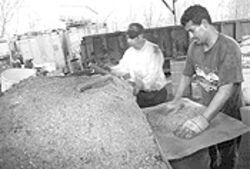 Workers Isaro Mendoza (left) and Mario Chavez sort metal waste at B&amp;B.