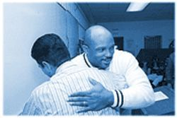 Hugging a friend is Tommie Dorsett, IFI program director, who supervises about 200 inmates.