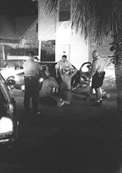 Late at night in Galveston, Officer Owens (right) and others check stories.