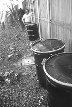David Rosenfield surveys his ruined backyard. The barrels hold contaminated soil.