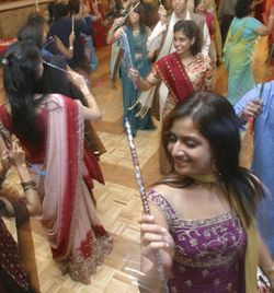 Guests party it up, dancing with dandia sticks at the Friday night sangeet.