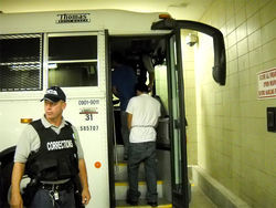A bus for private prisons giant Corrections Corporation of America picks up migrants sentenced to time in custody by a Tucson magistrate.