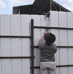 An anti-horse-slaughter activist films workers over the fence at Dallas Crown.