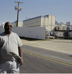 Robert Eldridge, who lives downwind of Dallas Crown, fought to shut the plant down. Behind him, airline shipping containers wait to carry meat to Europe.