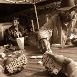 Enith Brown, foreground, spreads his dominos while sending Clyde Hendricks to the boneyard the night before the trail ride.