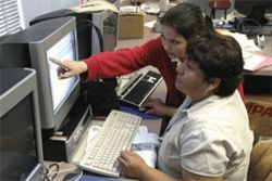 Student Jessica Martinez helps Maria Gonzales during a computer technology class at Eastwood Academy.