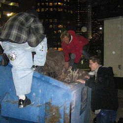 Steve Shreve and his crew check a Dumpster for their stuff, which is missing from their spot near the highway, but most of it is gone. They lost food, clothes and medication.