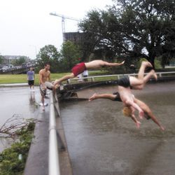 Jack Lafferty, Simon Cahill and Alex Burian jump into the river that Allen Parkway became.