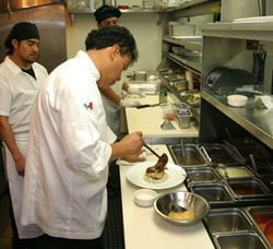 Hugo plates food with his kitchen staff.