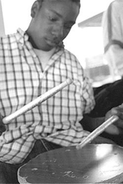 Bayousphere Practicing patience: Smiley High School junior Kevin Harris drums a stool as he waits for a ride home from school. Harris plays snare in the concert and marching bands.