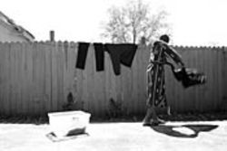 James washes his clothes in the shower and hangs  them on the fence to dry.