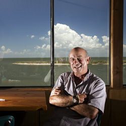 From the top floor of his Stingaree Restaurant, local attorney and restaurateur Jim Vratis is helping lead the Bolivar Peninsula back from the brink. Behind him is Goat Island, where several of the area's storm victims washed up.