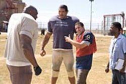 The Longest Yard (with Adam Sandler and  Chris Rock, right) is like a cover song by a tone-deaf  performer.