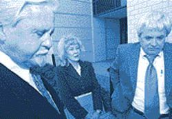 Shelton arrives with attorneys Randy Taylor (left) and Jerry Cobb for a hearing on the stalking charge.