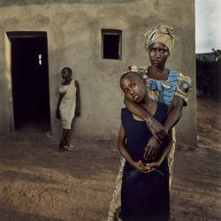 Valentine stands with her daughters Amelie and Inez in Rwanda by Jonathan C. Torgovnik