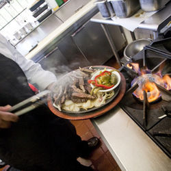 Ninfa's fajitas are cut against the grain and served on a sizzling comal with onions and peppers.