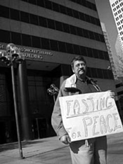 Ben Wagner, with The Houston Coalition for Justice, Not War, does his day in front of the federal building.