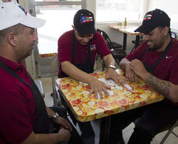 "Luis Roque, playing dominoes with Angel Lajara, left, and William ""Papito"" Lopez — co-workers at Tex-Chick — is one of approximately 30,000 Puerto Ricans in Texas, which has become the third most popular destination for educated Puerto Ricans in recent years."