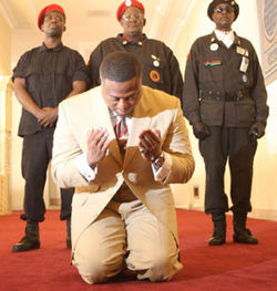 Seldom without a crowd, Quanell X keeps his bodyguards close while praying at the Islamic Da&#039;wah Center.