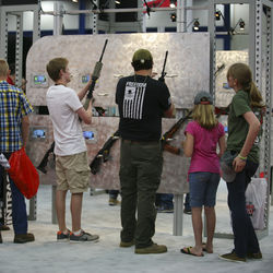 A family peruses one of the convention's many gun displays dotted throughout the sprawling Houston convention center.