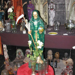 "Officer ""J.G."" Garza of the Houston Police Department's Narcotics Division says he almost always  finds a Santa Muerte altar inside the home of drug suspects. This photograph was taken in a cartel safe house in Houston."