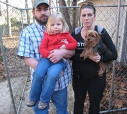 "Erik and Rosalyn Frazier, with their two-year-old daughter Reagan, and another one of their dogs, a Yorkshire terrier named Olly, claim it became their new neighbor's ""sole purpose in life to have our dog killed."""