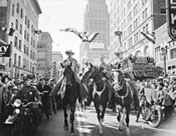 Singing cowboy Gene Autry (center) gets a horse and a motorcycle escort in the 1942 rodeo parade.