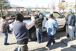 Workers hop into a contractor&#039;s truck before wages 