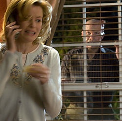 Starla Grant (Elizabeth Banks) dials 911, while gruesome Grant Grant (Michael Rooker) looks on.
