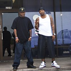 Ganksta NIP (right) and Candyman work the grind outside Studio 360 barbershop.