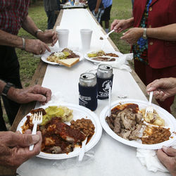 Some folks prefer to enjoy their barbecue plates at the stand-up tables under the shade trees.