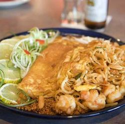 The stellar pad Thai is covered with an omelet.