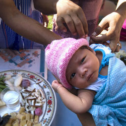 Red and white threads are tied around the wrist of a Burmese infant to signify unity for ethnic Karen people now scattered across the globe.