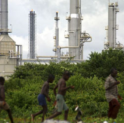 People scavenge on refuse near an oil facility in Nigeria.