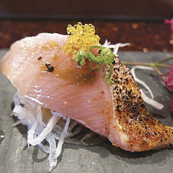 Seared hamachi belly sashimi topped with yuzu flying fish eggs and a wasabi-yuzu-ume plum paste at Zushi.