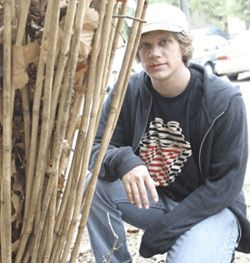 Jordan Johnson crouches alongside his outdoor bamboo sculpture on the HSPVA campus in Montrose.