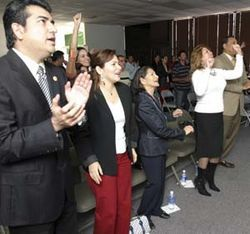 Believer Boris Martinez (far left) applauds in a nondescript Sharpstown warehouse...