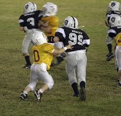 The 4-foot-1, 72-pound Joshua tries to block #99, but Evan Whaley of the Raiders just brushes him aside.