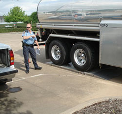 A Houston police officer checks the weight of a tanker truck.